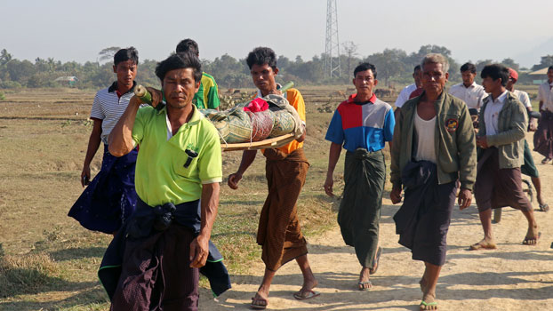 Myanmar residents carry the body of an ethnic Rakhine woman for burial in Rathedaung township after fresh fighting between the Myanmar military and the Arakan Army in western Myanmar's Rakhine state, Feb. 21, 2019.
