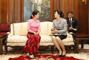 Aung San Suu Kyi (L) speaks with Thai Prime Minister Yingluck Shinawatra in Rangoon, Dec. 21, 2011.