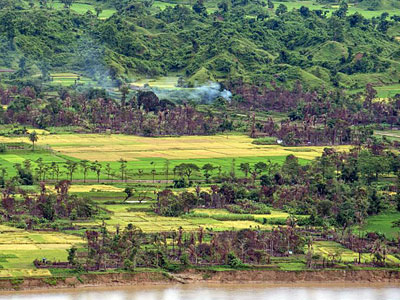 Smoke billows from a burned village near Maungdaw township in Myanmar's volatile northern Rakhine state, Sept. 27, 2017.