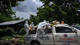 Volunteers wearing PPE transport the body of a victim of COVID-19 to a cemetery in Hlegu township in Yangon, July 10, 2021.