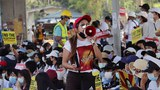 A Myanmar anti-junta protester uses a megaphone to address fellow demonstrators at a rally at the Myae Ni Gone juntion in Yangon, Feb. 23, 2021.