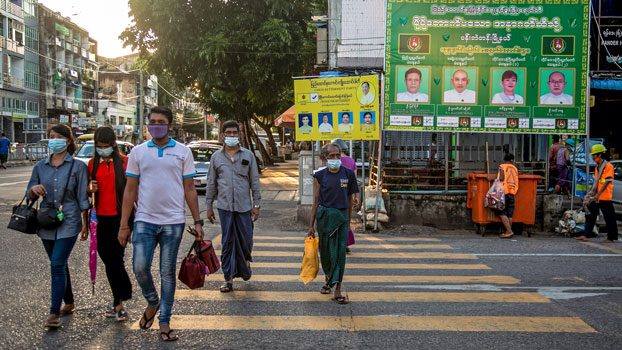 Pedestrians walk past election campaign posters as they cross a road in Myanmar's commercial hub Yangon, Oct. 7, 2020.