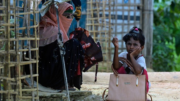 A Rohingya refugee girl waits for transportation with her mother at the Kutupalong refugee camp in Ukhia, Cox's Bazar district, southeastern Bangladesh, Oct. 15, 2020.
