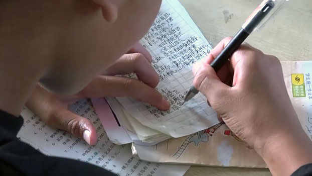 An ethnic Mongla boy writes Chinese characters in a notebook in the Mongla autonomous special region of eastern Myanmar's Shan state, July 2019.