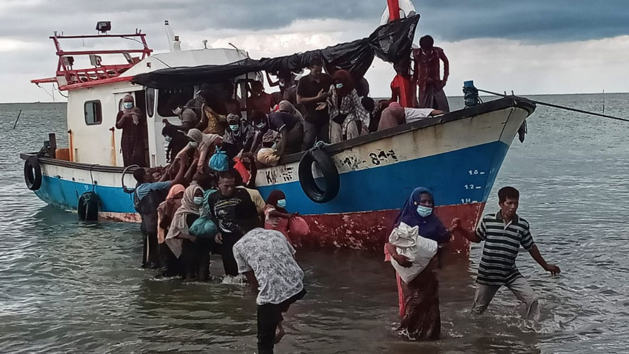 Rohingya women are helped ashore in North Aceh, Indonesia, June 25, 2020.