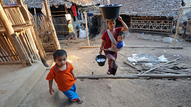 Ethnic Karen refugees walk past shelters inside the Mae La refugee camp in Mae Sot near the Thai-Myanmar border in a file photo.