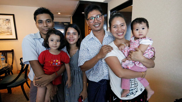 Reuters Myanmar reporter Kyaw Soe Oo (L) poses with wife Chit Su Win (3rd from L) and their daughter, along with Reuters reporter Wa Lone (3rd from R) and his wife Pan Ei Mon (2nd from R) and their daughter, after being freed from Insein Prison in Yangon under a presidential amnesty, May 7, 2019.