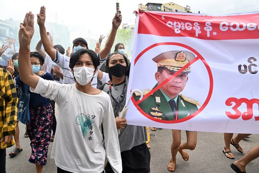 Protesters make the three-finger salute beside a banner featuring junta leader Min Aung Hlaing  in a demonstration against the military junta in Yangon, July 3, 2021. Credit: AFP