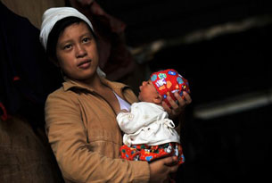 A Kachin woman holds her baby at a relief camp in Laiza, Sept. 21, 2012.