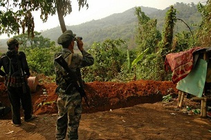 A Kachin Independence Army soldier looks through binoculars at Burmese army positions from an outpost near Laiza, May 12, 2012.