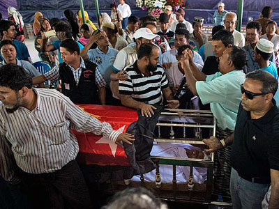Mourners arrive to pay their last respects over the coffin bearing Ko Ni, a prominent Muslim lawyer in Myanmar who was shot dead, at his funeral in Yangon, Jan. 30, 2017.
