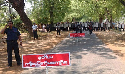 Security forces stand behind a sign warning protesters not to go any further, April 26, 2013. Photo credit: RFA.