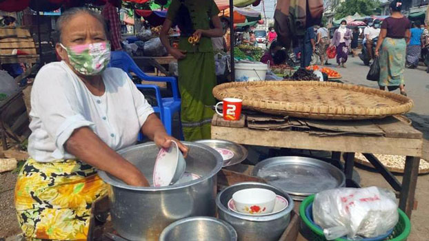 A Myanmar food vendor wearing a protective face mask washes dishes at a public market in the central Myanmar city of Mandalay, April 2020.