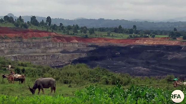 Mountains of coal are piled near a pasture in Tigyit village, Pinlaung township, in Myanmar's northern Shan state, August 2019.