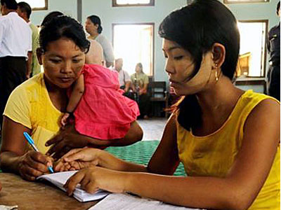 A Myanmar woman is given a document declaring her an illegal squatter of a ward in Yangon's Bahan township, June 12, 2017.
