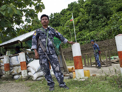 Myanmar border police stand guard at a checkpoint near the entrance of Maungdaw township in western Myanmar's Rakhine state, Aug. 28, 2017.