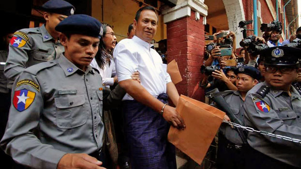 Aung Win Zaw (C), who helped plan the murder of prominent Muslim lawyer Ko Ni, is escorted by police from the Yangon Northern District Court in Yangon, Feb. 15, 2019.