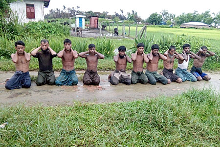 Ten Rohingya men with their hands bound kneel in Inn Din village of Maungdaw township, western Myanmar's Rakhine state, Sept. 1, 2017.