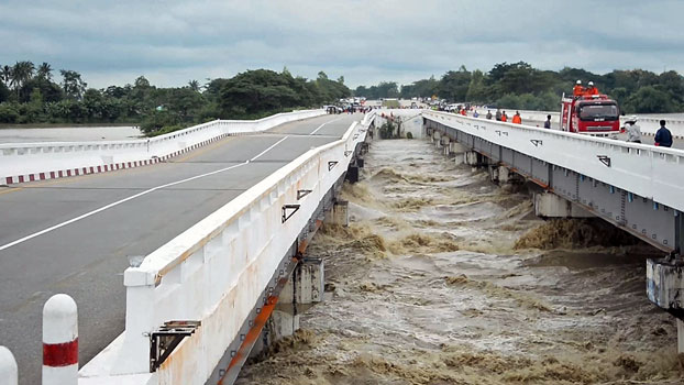 A bridge along the Yangon-Mandalay highway is damaged by raging floodwater in the Swar River in central Myanmar's Bago region, Aug. 29, 2018.