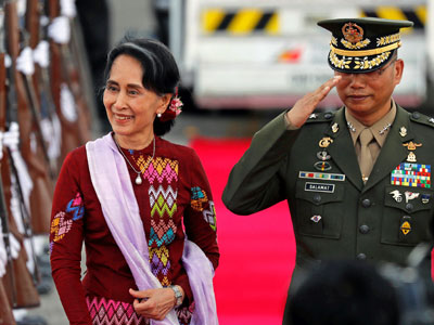 Myanmar State Counselor Aung San Suu Kyi walks with a Filipino military officer upon her arrival in Pampanga province, the Philippines, to attend the Association of South East Asian Nations summit and related meetings in the capital Manila, Nov. 11, 2017.