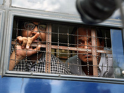 Myanmar interpreter Aung Naing Soe (L) and driver Hla Tin (R) look out from a prison transport vehicle after they are sentenced to two months in prison for illegally flying a drone, in a court in Naypyidaw, Nov. 10, 2017.