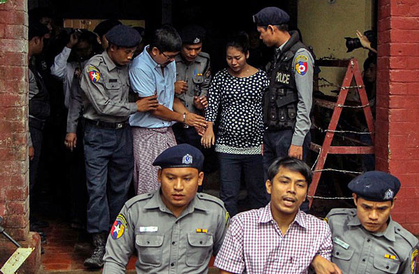 Detained Myanmar journalists Kyaw Soe Oo (front-C) and Wa Lone (back-2nd from R) are escorted by police from a courthouse following a hearing in Yangon, Myanmar, July 9, 2018.