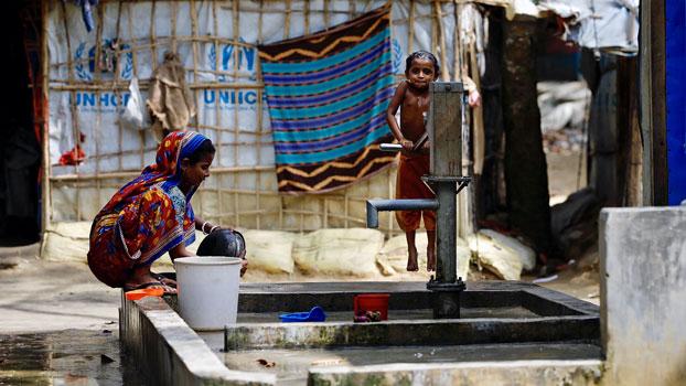 Hindu Rohingya refugees from western Myanmar's Rakhine state pump water in a refugee camp in southeastern Bangladesh's Cox's Bazar district, Nov. 13, 2018.