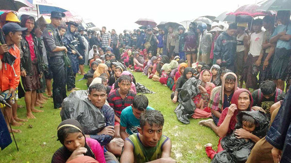 Rohingya refugees from Bangladesh sit in the rain after they and their wrecked boat washed up on a beach in Rathedaung township, western Myanmar's Rakhine state, June 12, 2018.