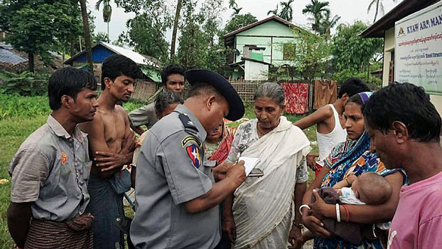 Myanmar Hindus speak to a Myanmar police officer at a makeshift camp after fleeing violence in Maungdaw township, western Myanmar's Rakhine state, Aug. 30, 2017.