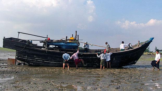 Myanmar local officials check the abandoned boat of Rohingya Muslims who washed ashore in Kyauktan township  south of Yangon, Nov. 16, 2018.