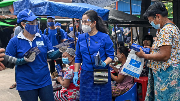 Thet Thet Khine (C), chairwoman of the People's Pioneer Party, hands out campaign literature to vendors during the launch of the party's campaign ahead of Myanmar's general elections, in Yangon, Sept. 8, 2020.