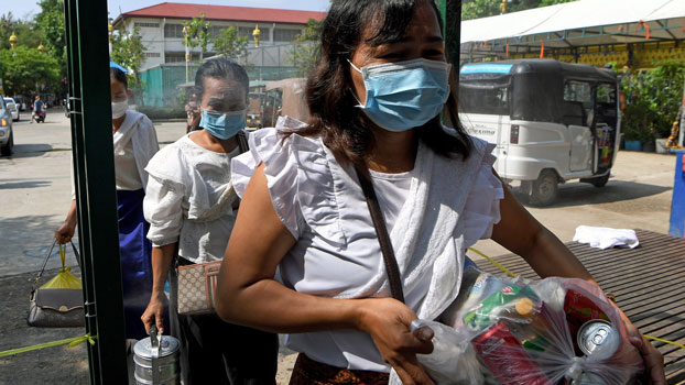 Cambodian women wearing face masks to protect themselves from the coronavirus walk through a gate equipped with disinfectant spray at a pagoda during the Khmer New Year in Cambodia's capital Phnom Penh, April 14, 2020.