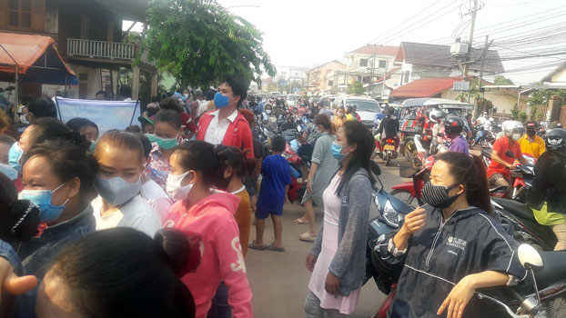 People gather to pick up packages of donated food during the Lao New Year in Dondeng village, Chanthabouly district, in the capital Vientiane, April 14, 2020.