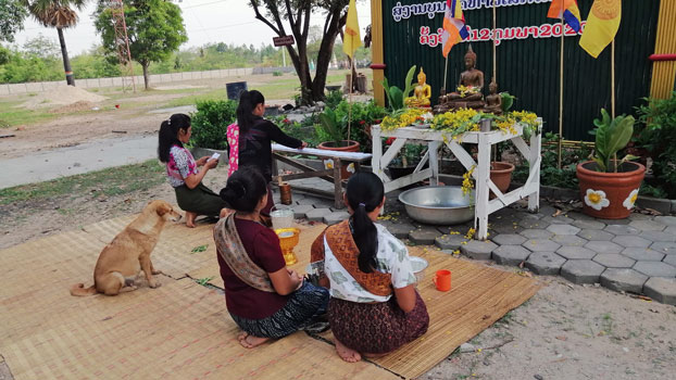 Women quietly honor Buddha during the Lao New Year outside a closed temple in Baan village, Songkhone District. in southern Laos' Savannakhet province, April 2020.