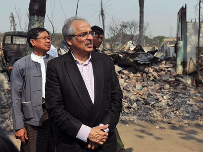 Vijay Nambiar (C), the United Nations special adviser on Myanmar, looks at destroyed buildings following an outbreak of communal violence in central Myanmar's Mandalay region, March 24, 2013.