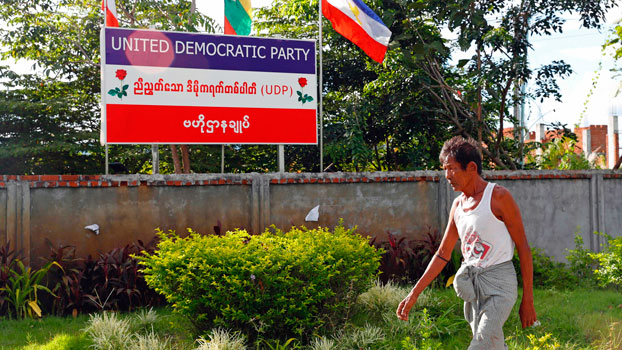 A man walks past a billboard of the United Democratic Party outside the party's headquarters in Myanmar's capital Naypyidaw, Sept. 30, 2020.
