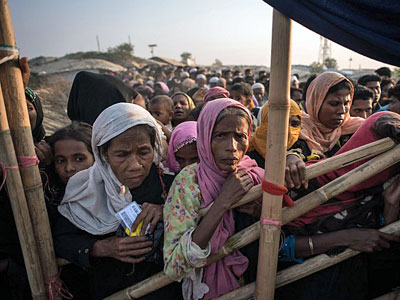 Rohingya Muslim refugees from Myanmar wait to be called to receive food aid of rice, water, and cooking oil in a relief center at the Kutupalong refugee camp southeastern Bangladesh's Cox's Bazar, Nov. 28, 2017.