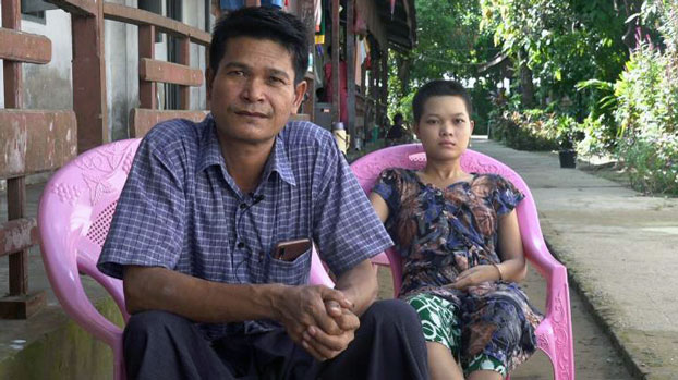 Hnin Yu Hlaing (R) sits beside her father, Maung Phyu Thee, at the Alo Taw Pyay Buddhist monastery compound in Sittwe, western Myanmar's Rakhine state, Oct. 28, 2020.
