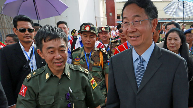 Myanmar ethnic rebel leader General Gun Maw (L) from the Kachin Independence Army walks with Chinese special envoy Sun Guoxiang (R) as representatives of various Myanmar ethnic rebel groups arrive for the opening of a conference in Mai Ja Yang, northern Myanmar's Kachin state. July 26, 2016.