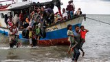 Locals evacuate Rohingya from a boat after it arrived on the coast of North Aceh, Indonesia, June 25, 2020.