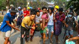 A protester who was injured during a crackdown by security forces on a demonstration against the military coup is carried to safety in Yangon, March 14, 2021.