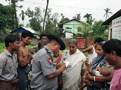 Myanmar Hindus speak to a Myanmar policeman at a makeshift camp after fleeing violence in Rakhine state's Maungdaw township, Aug. 30, 2017.