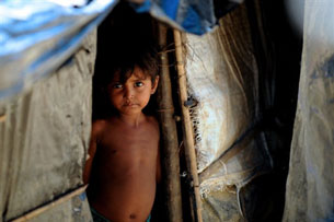 A Rohingya refugee child stands in a shelter in an unregistered camp at Kutupalong, Sept. 1, 2009.
