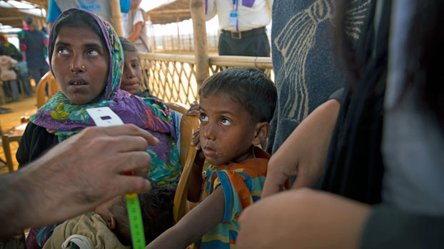 A Rohingya boy (C) from Myanmar looks at a UNHCR volunteer who takes his measurement following his arrival at the Balukhali refugee camp about 32 miles from Cox's Bazar in southeastern Bangladesh, Jan. 14, 2018.