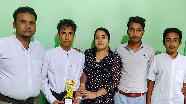 Rohingya student Muhammad Ayaz (2nd from L) holds a trophy he received in recognition of his scholastic achievements as he stands beside his parents and brothers at their home in Buthidaung town, western Myanmar's Rakhine state, in an undated photo.