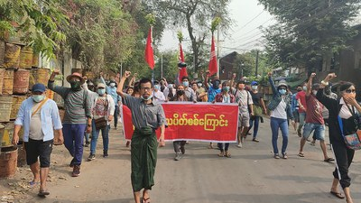 Protesters holding a banner as they march during a demonstration against the military coup in Mandalay, April 10, 2021.