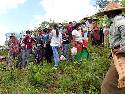 Villagers watch while corpses are removed from shallow graves in Long Mon village of Mong Yaw subtownship in Myanmar's northern Shan state, June 30, 2016.