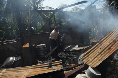 A Muslim man inspects the burnt area of a vandalized building in Thabyuchine village in Thandwe, Oct.  3, 2013. Photo credit: RFA.
