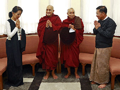 Myanmar's State Counselor Aung San Suu Kyi (L) and military commander-in-chief Senior General Min Aung Hlaing (R) pay their respects to two Buddhist monks to commemorate Martyrs' Day in Yangon, July 19, 2016.