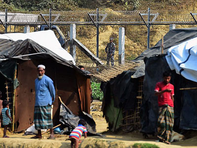 A Myanmar security guard keeps watch along the Myanmar-Bangladesh border as Rohingya refugees stand outside their makeshift shelters near Tombru in southeastern Bangladesh's Bandarban district, March 1, 2018.